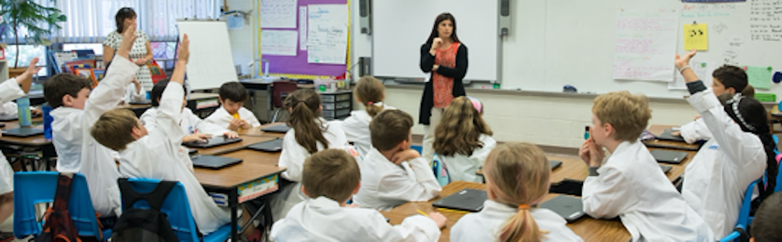 Students in white lab coats are in a science classroom with their hands raised.