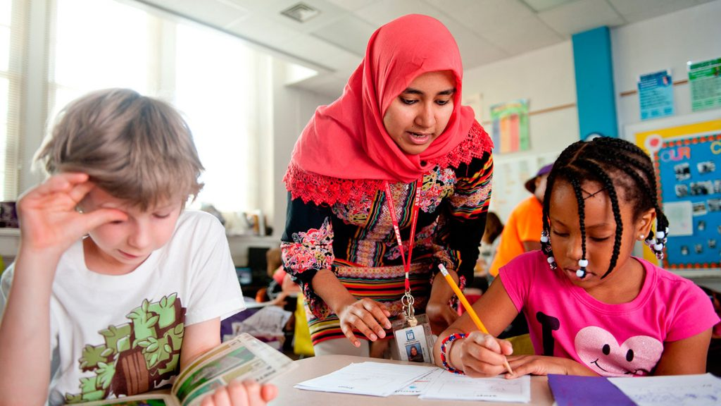 Teacher leans over table with students reading and writing
