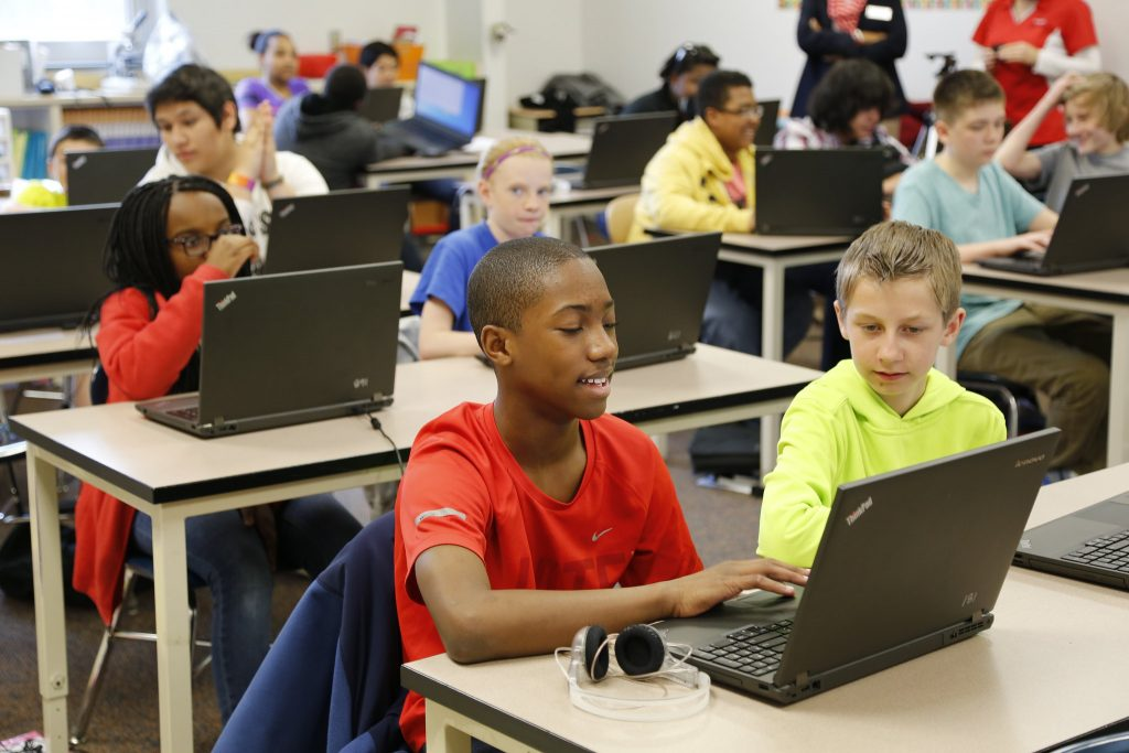 Student work on laptops in a classroom