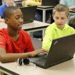Two students work on laptops in a classroom