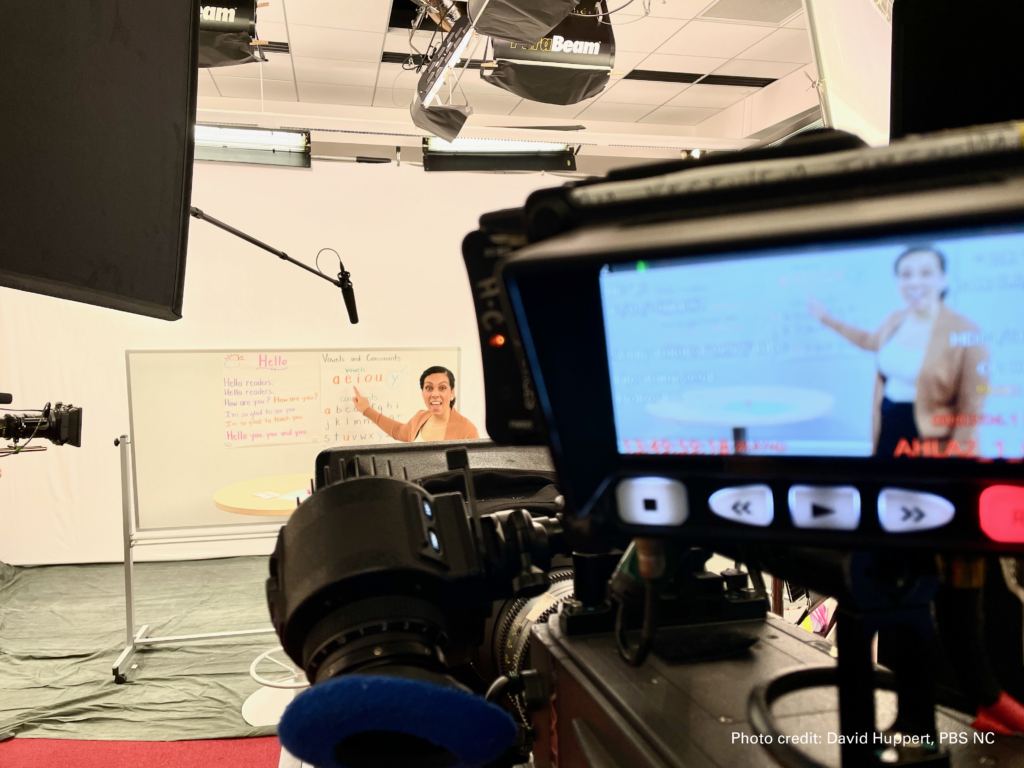 In the foreground, a television camera monitor shows what is happening in the background: A woman pointing at a dry-erase board.