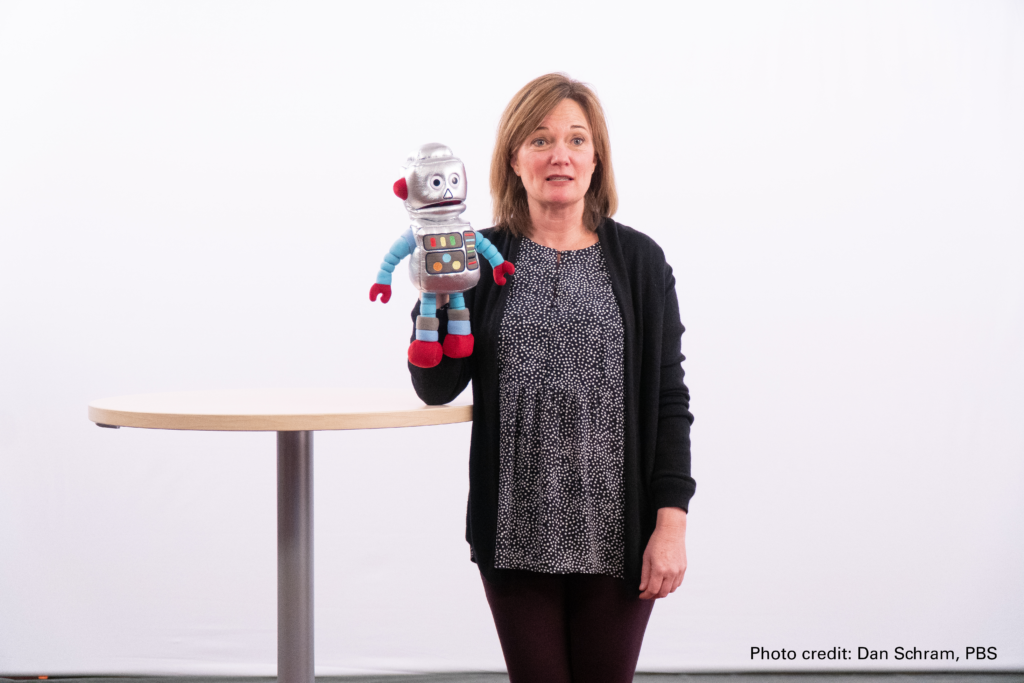 A woman holds up a plush robot toy in front of a white screen