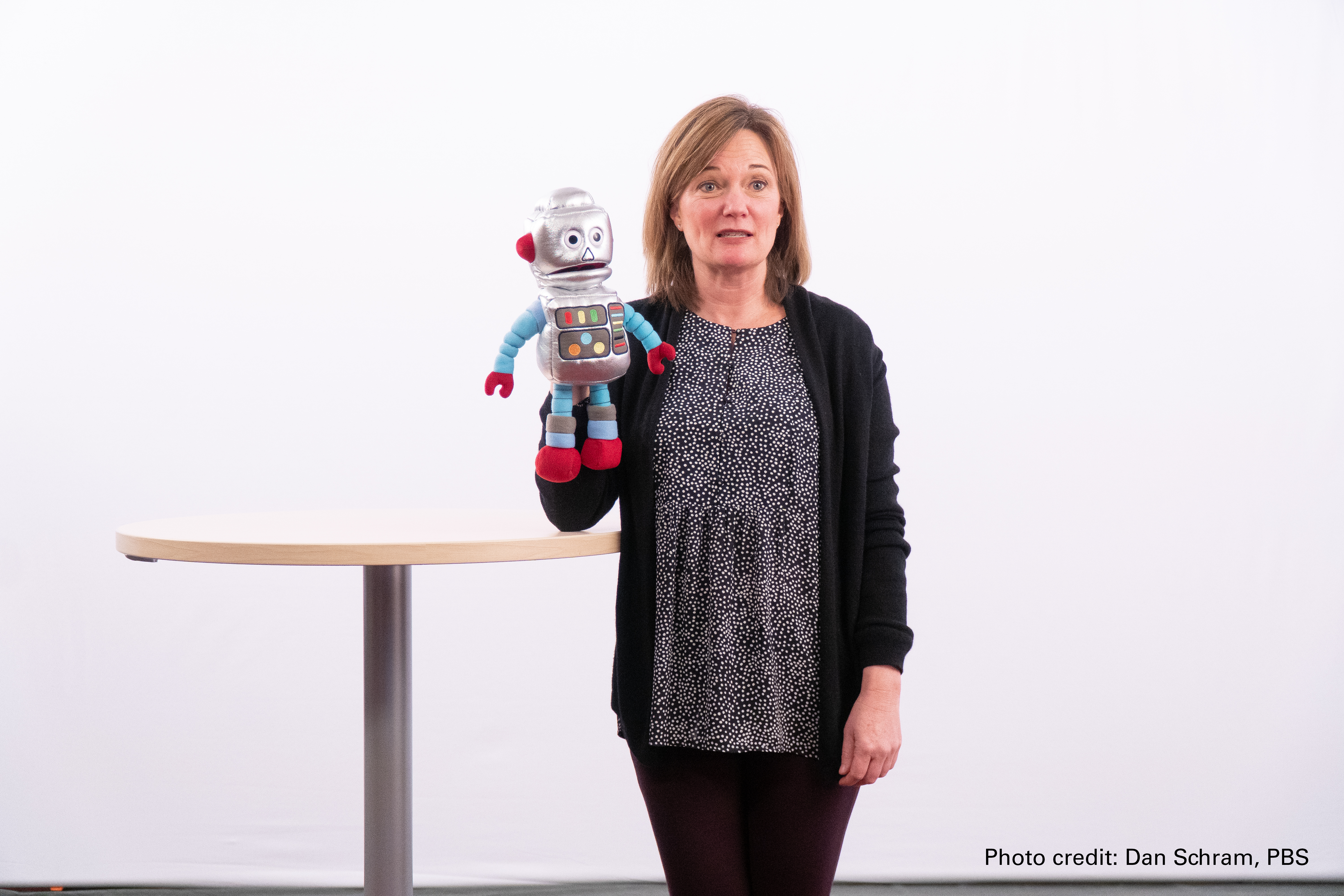 A blonde woman holds up a plush robot toy in front of a white screen