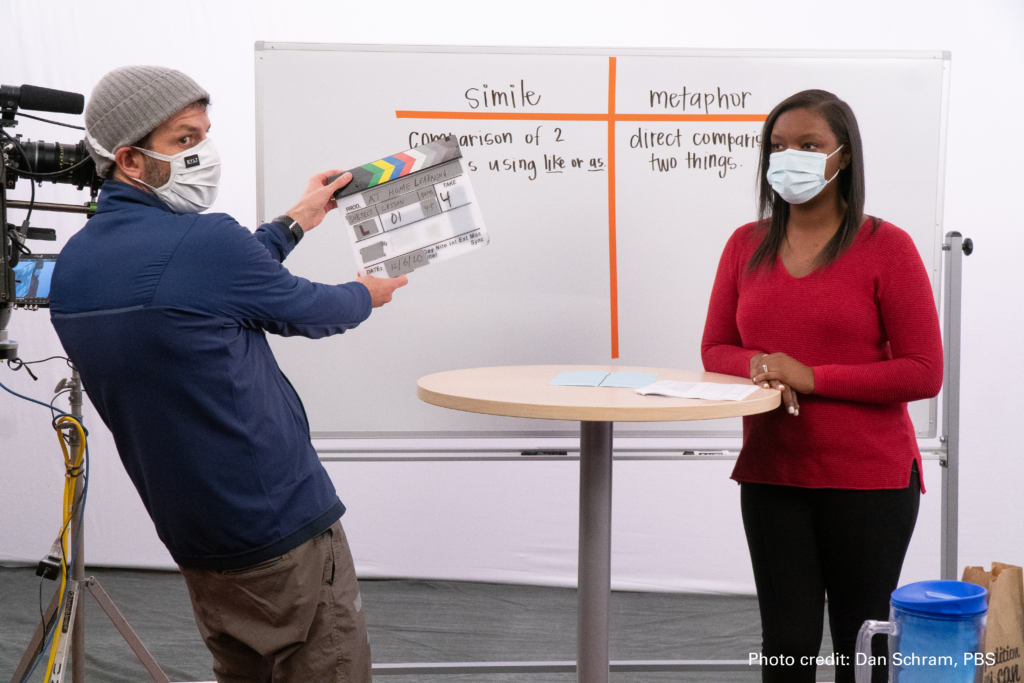 A woman and man wear cloth masks on a television set. The man is holding up a clapperboard.