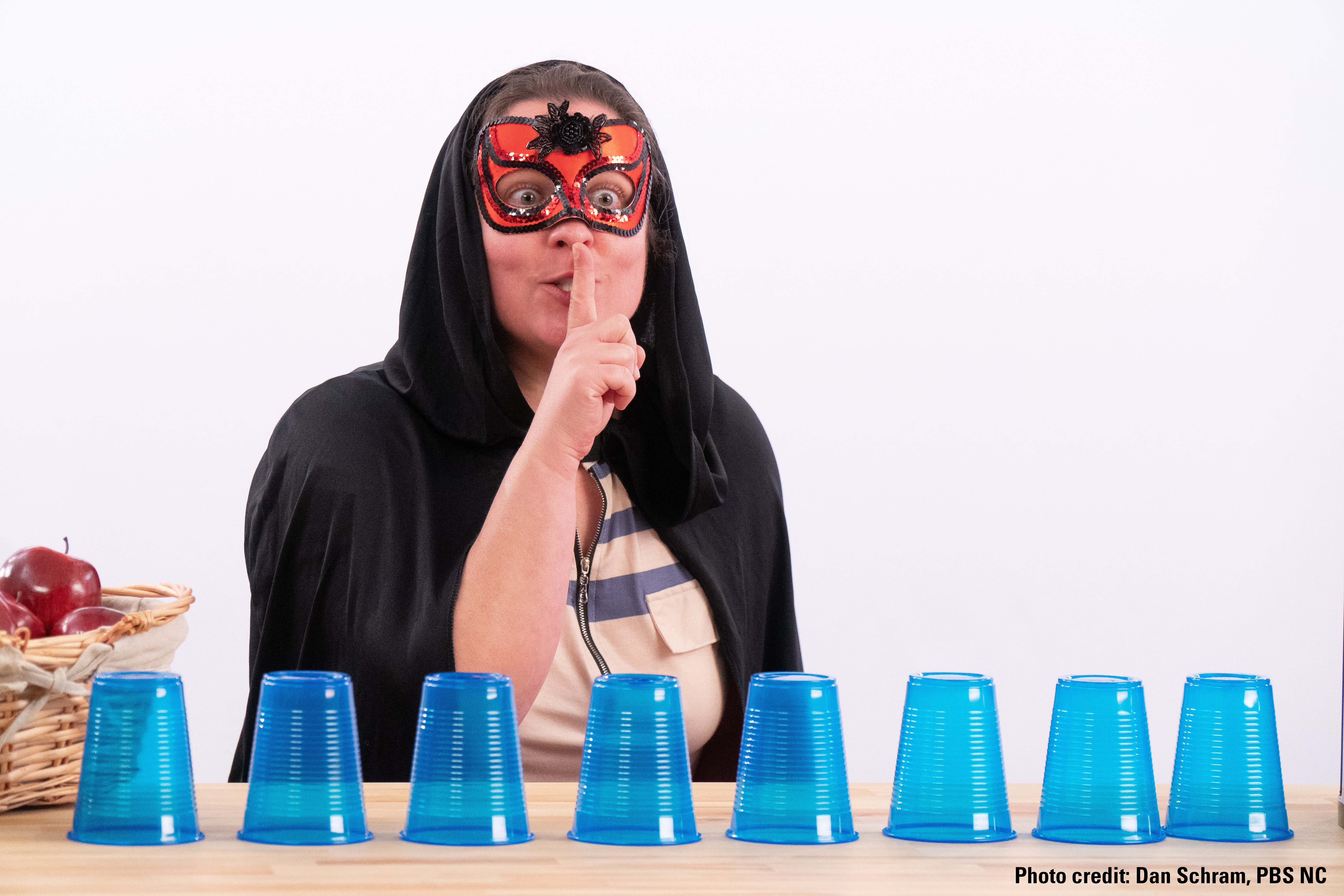 """A woman is dressed as a burglar in a mask and cape. She has her index finger over her mouth to indicate """"quiet"""" and stands in front of a table with a line of upside down plastic blue cups."""