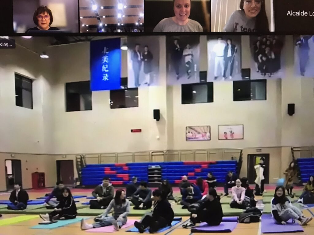 A screenshot of a teachers practicing yoga on mats in the SNA gym while NLC team members watch on Zoom