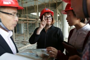 Dr. Hiller Spires discusses designs for SNA with colleagues on the construction site for the school. All those pictured are wearing red hard hats.