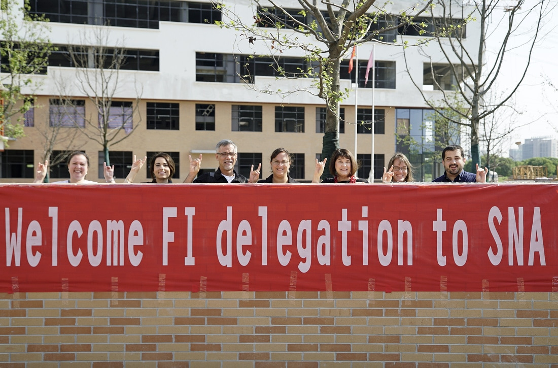 """The New Literacies Collaborative team stands behind a sign in front of SNA that says """"Welcome FI delegation to SNA!"""""""
