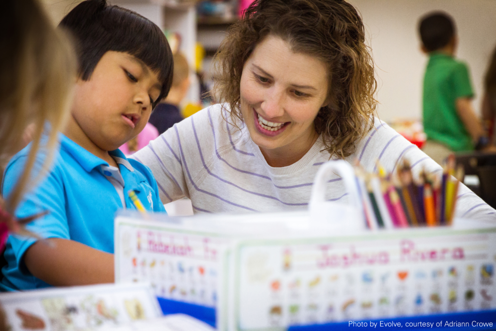 A teacher works with a student in her classroom as he sits at a table with a pencil.