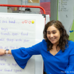 A teacher sits next to a whiteboard in a classroom and points to a list of ways to be kind