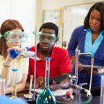 Students gather around a science experiment in a science classroom lab