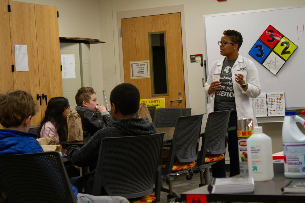A teacher in a white lab coat speaks to students while standing at the front of a science lab classroom